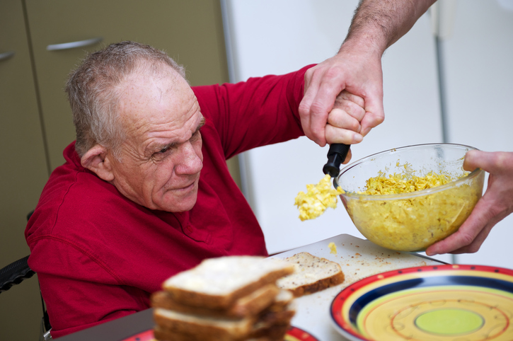 Senior Man with a Disability being helped in kitchen