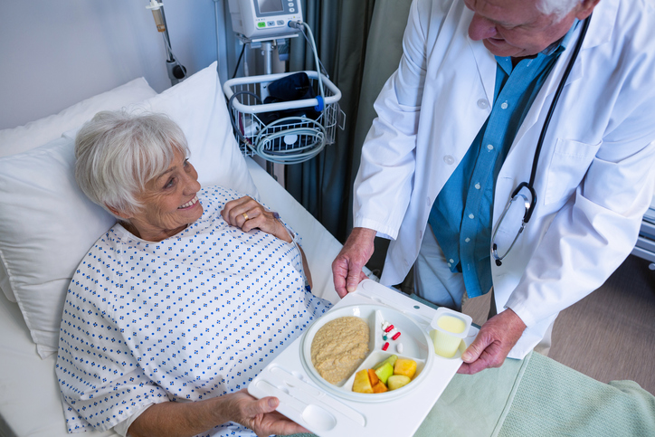 Doctor serving breakfast and medicine to senior patient