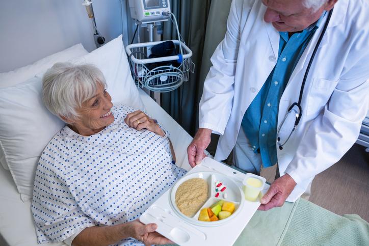 Doctor serving breakfast and medicine to senior patient