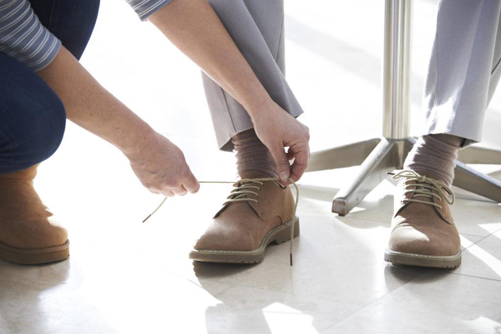 Adult Daughter Helping Senior Tie Shoelaces