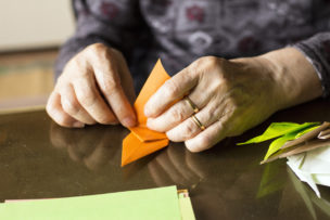 Hands of senior lady folding Origami paper