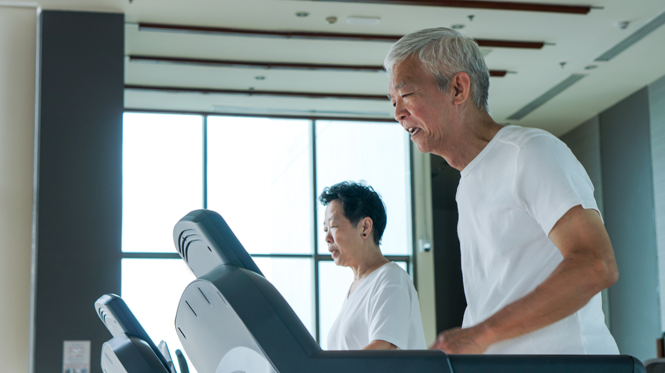 Old healthy Asian senior couple exercise together in gym running treadmill