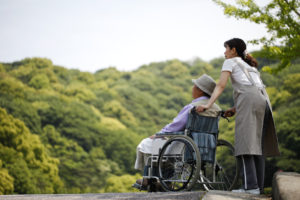 Senior in a wheelchair and helper