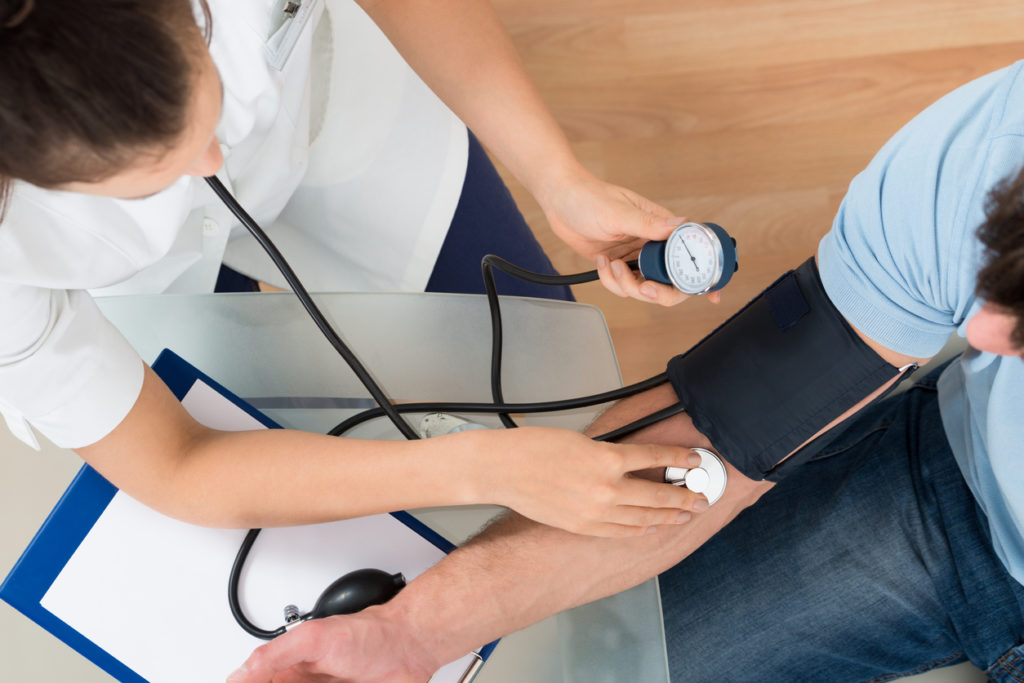 Doctor Measuring Blood Pressure Of Male Patient