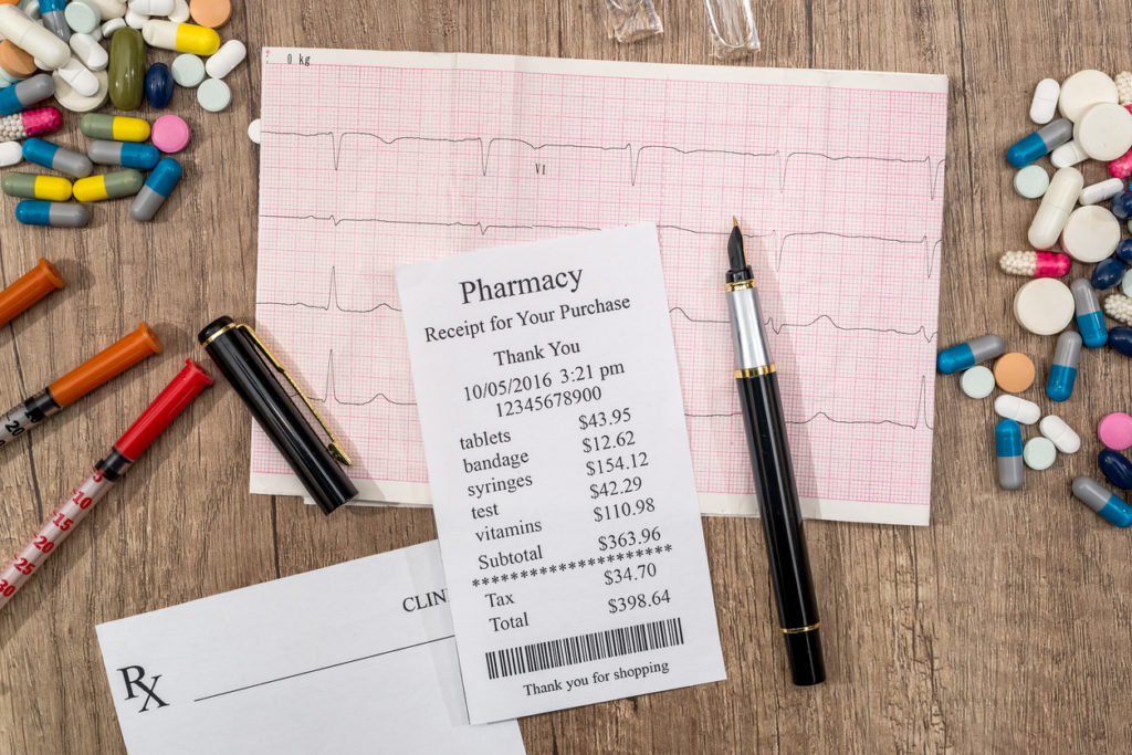 pharmacy receipt with egc, pills and syringe on desk.