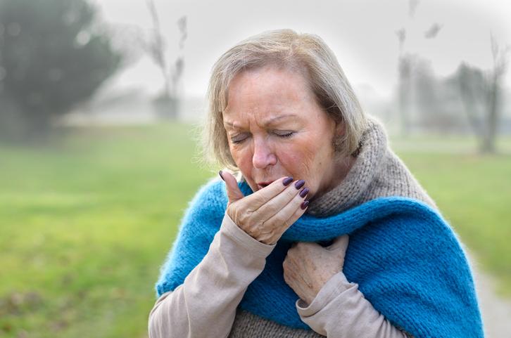 Elderly stylish woman coughing or sneezing