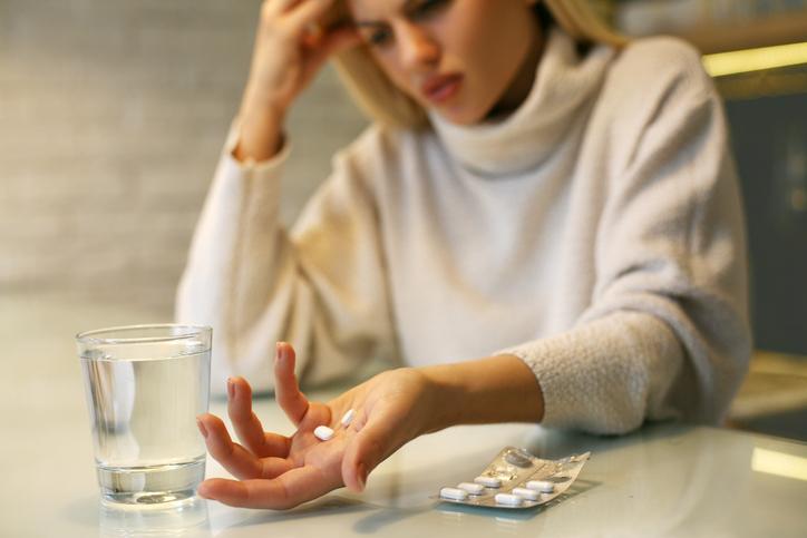 Pills in woman hands.