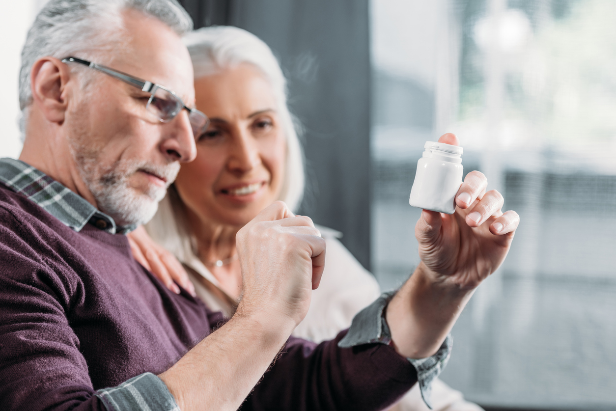 portrait of senior couple looking at pill bottle in hand