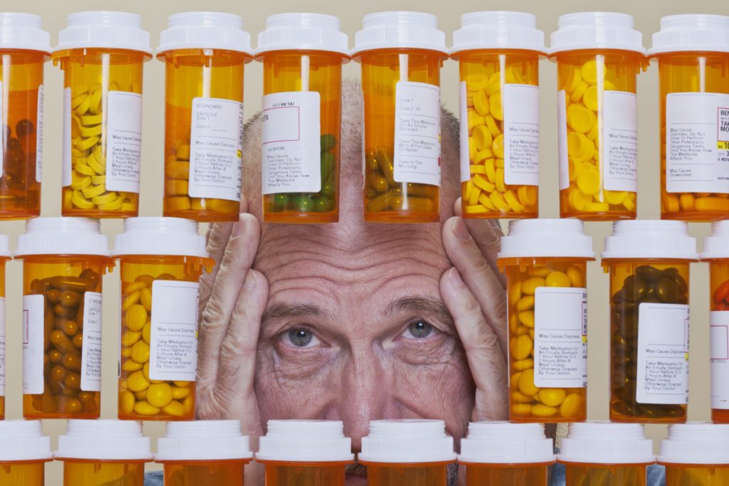 Depressed Senior Man Looking Through Rows of Prescription Medication