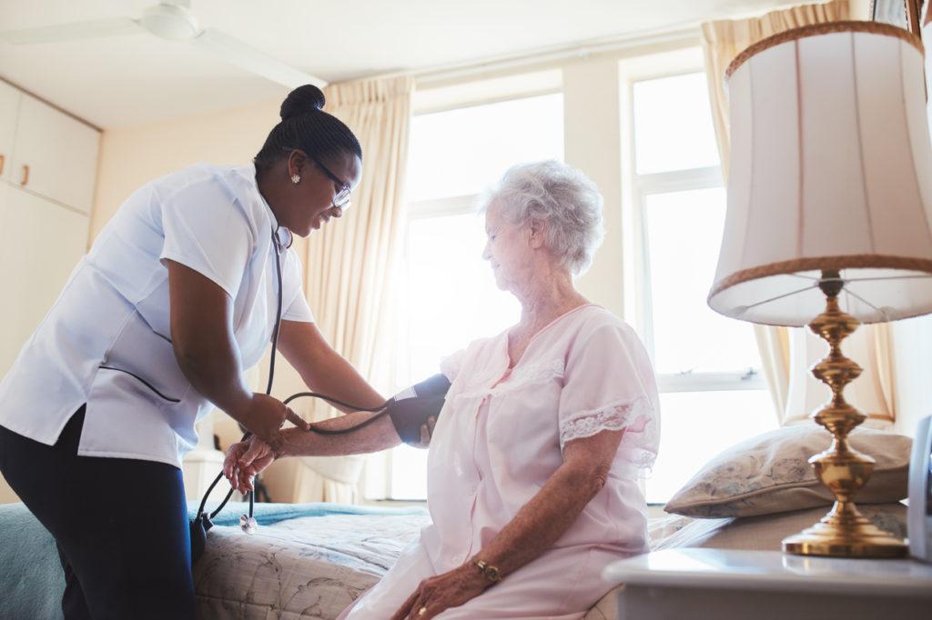 Nurse checking blood pressure of female patient