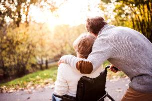Senior couple in wheelchair in autumn nature.
