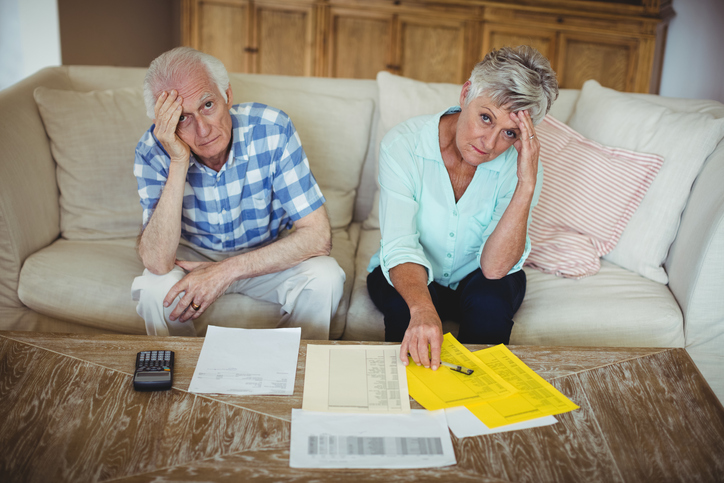 Portrait of worried senior couple checking bills in living room