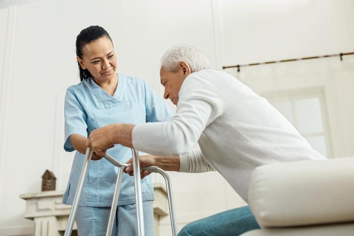 Joyful nice woman helping an elderly man