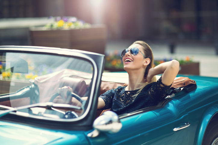 Fashion woman model in sunglasses sitting in luxury retro car