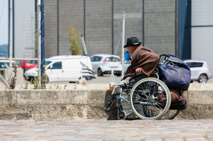 Homeless and disabled man sitting on wheelchair