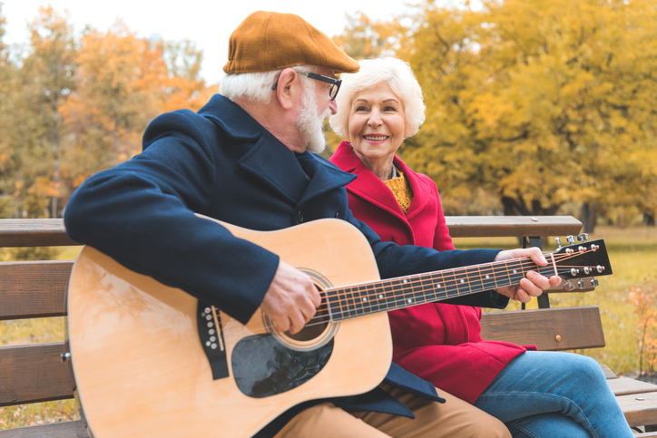 senior couple with guitar in park