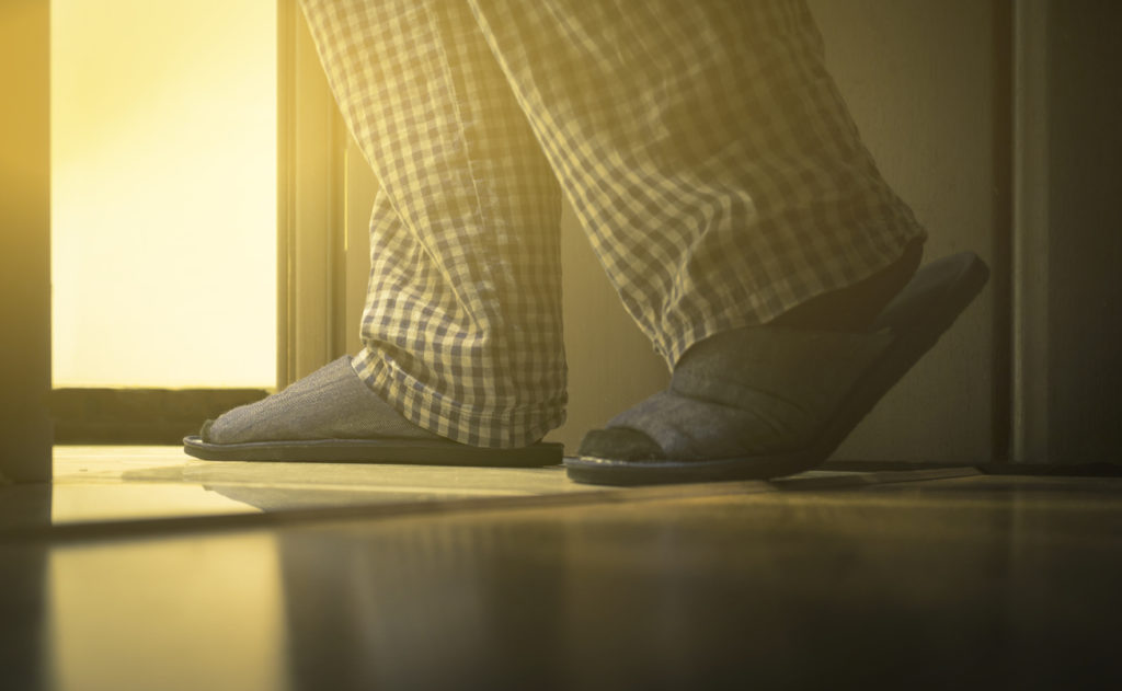 Adult man in pijamas walks to a bathroom at the night. Men's healths concept. Toned
