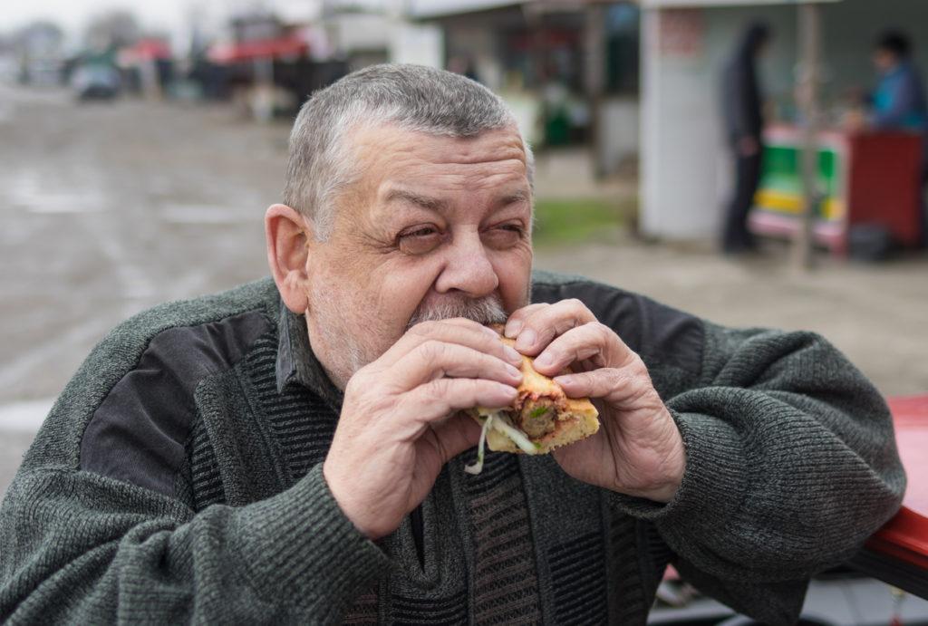Portrait of Caucasian senior driver eating lyulya kebab in lavash