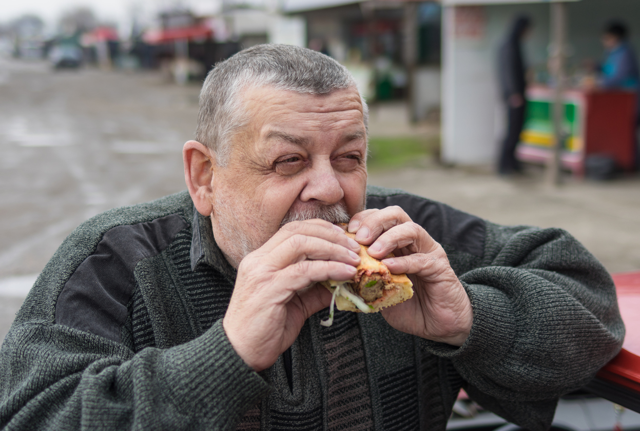 Portrait of Caucasian senior driver eating lyulya kebab in lavash