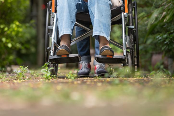 elderly woman in wheelchair walking with caregiver