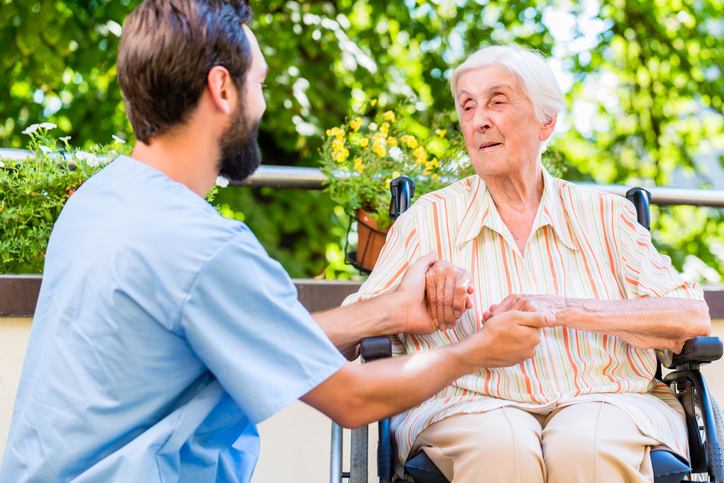 Geriatric holding hand of senior woman in pension home