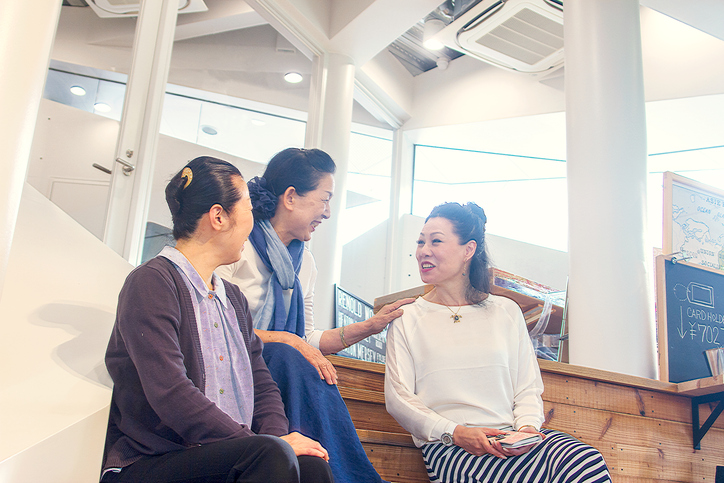 Three women sitting on stairs and chatting