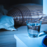Sleeping water on nightstand next to a glass of water. White tablet on table and bed in bedroom.