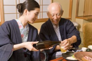 Woman pouring beer for senior man