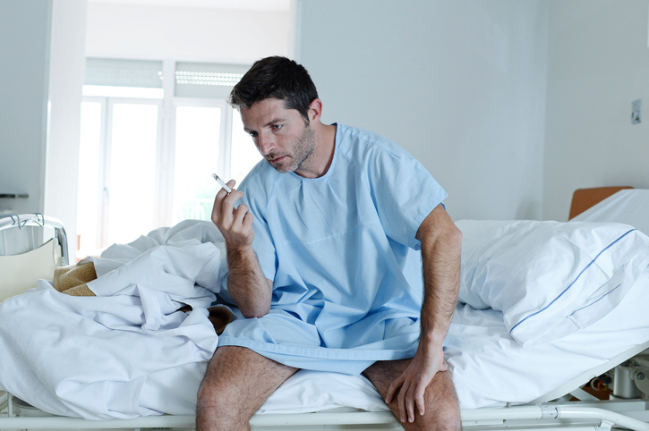 young attractive man looking sad worried at hospital bed smoking