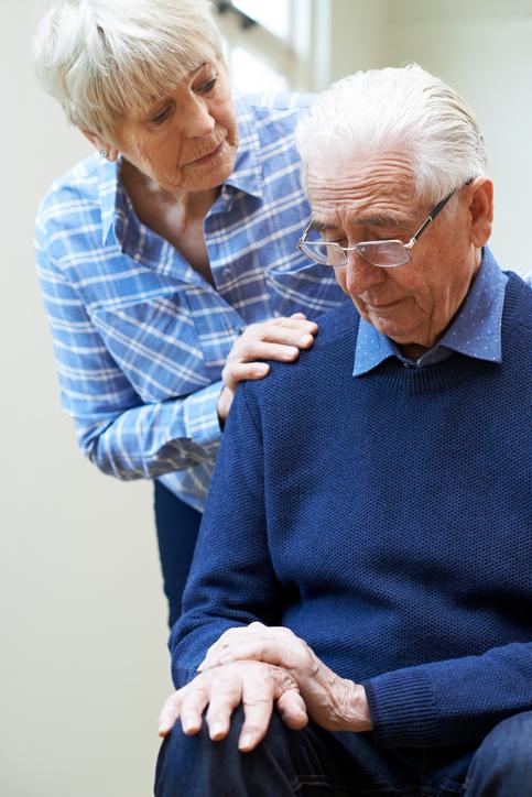 Senior Woman Comforts Husband Suffering With Parkinsons Diesease