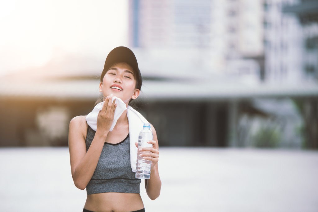 Wiping sweat Thirsty female jogger drinking fresh water after training. Young athletic woman exercising in the city park outdoors.