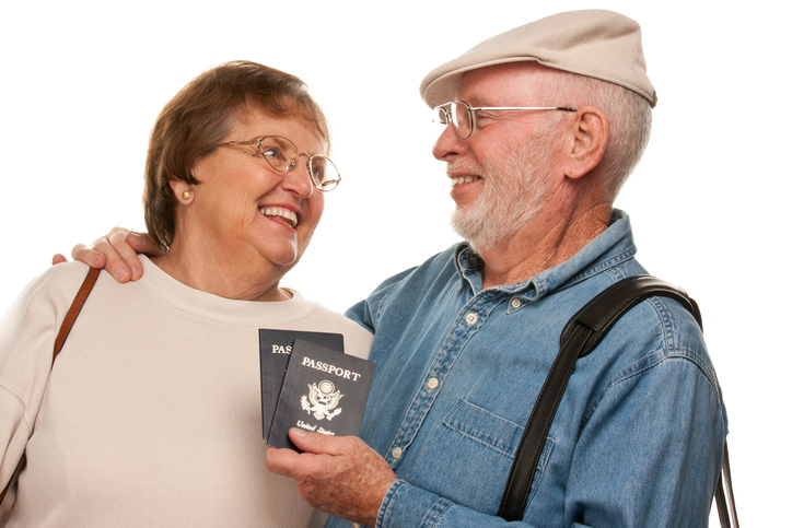 Happy Senior Couple with Passports and Bags on White