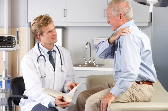 Doctor examining elderly male patient with pain in shoulder