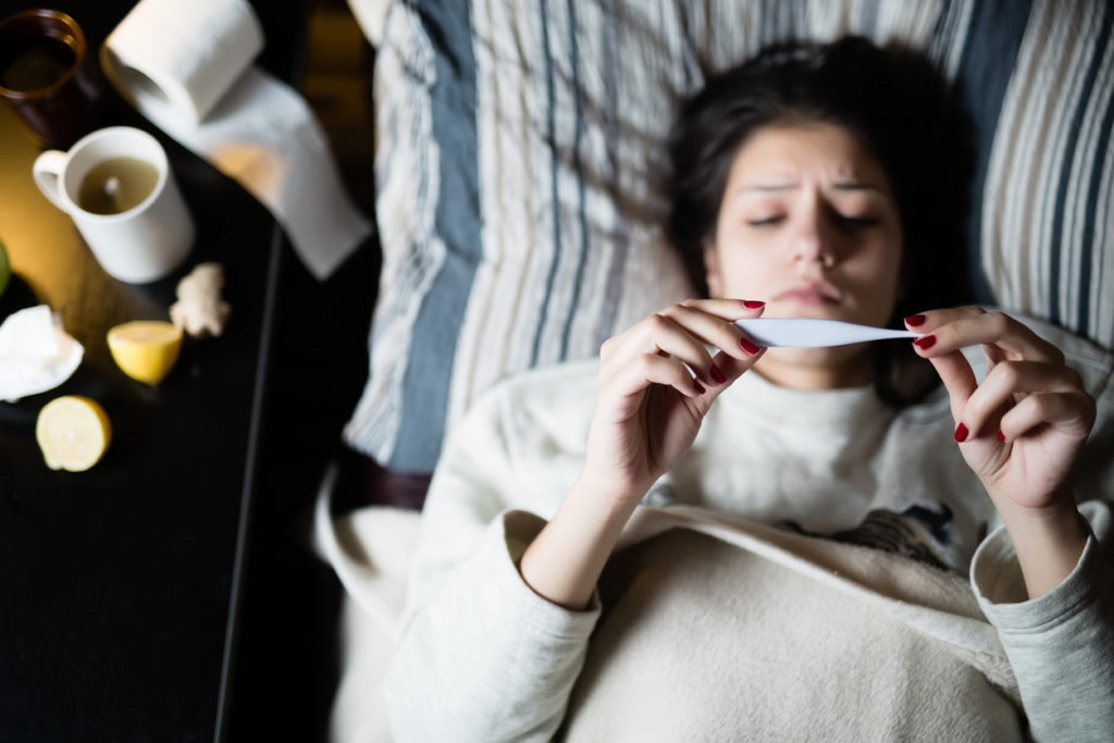 Flu.Woman Caught Cold.Virus.Sick woman laying in bed under wool blanket