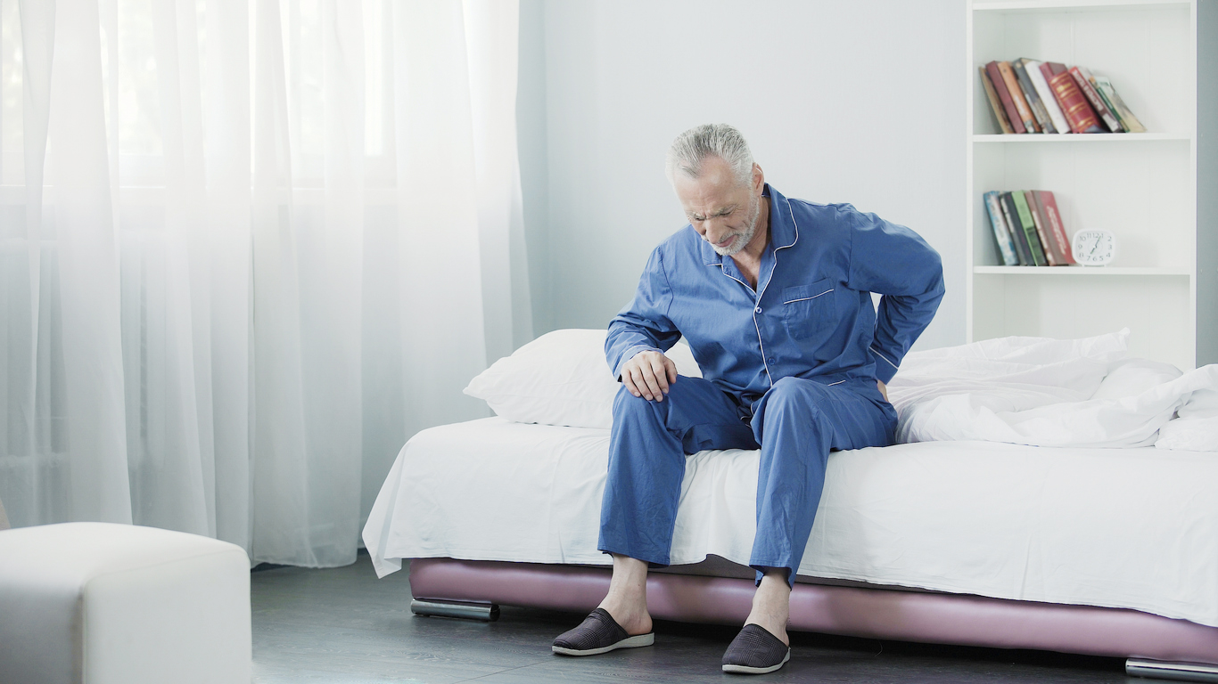 Retired man sitting in bed and feeling terrible pain in back, health and illness