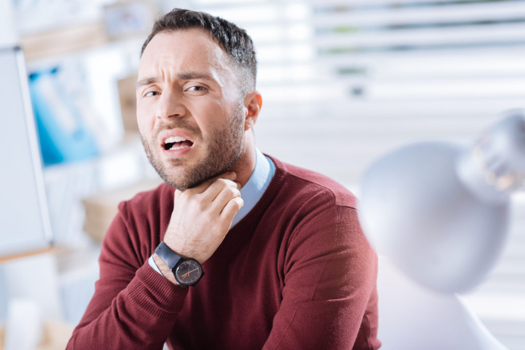 Emotional worker touching his neck and having a sore throat