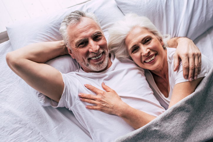 The happy elderly couple laying on the bed