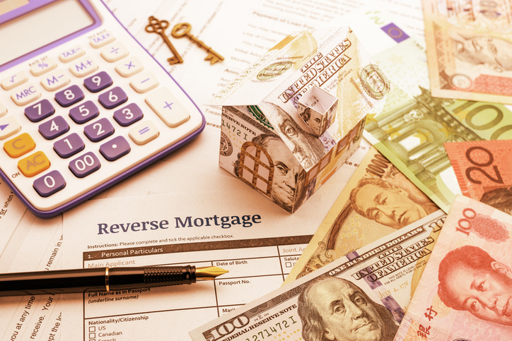 Fountain pen, brass keys, a calculator, a dollar paper house and a blank reverse mortgage form with banknotes.