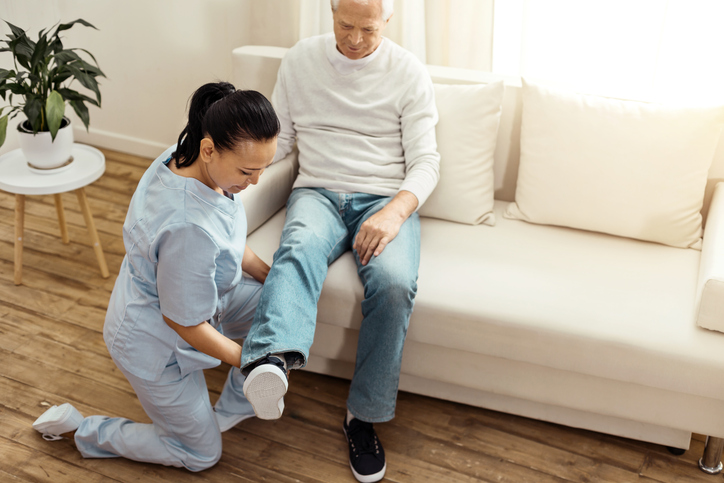 Professional experienced caregiver warming up her patients leg