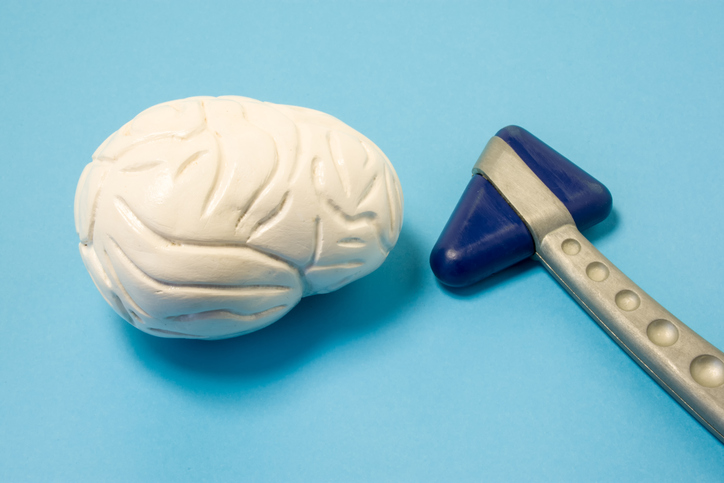 Diagnostic tool of neurologist - neurological rubber reflex hammer and model of human brain next to blue uniform background. Diagnosis and treatment of brain diseases of medical neurology specialist