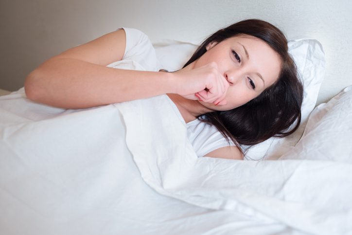 Sick woman feeling bad and lying in bed