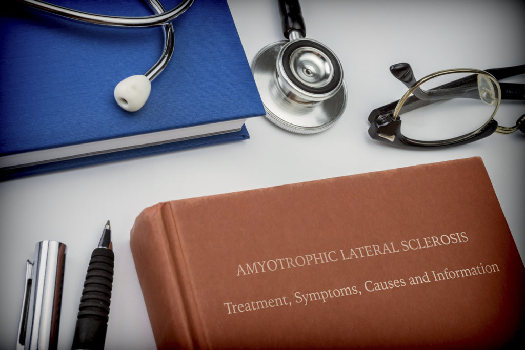 Titled book Amyotrophic Lateral Sclerosis along with medical equipment, conceptual image