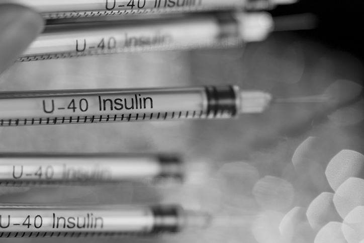 Insulin syringes on multicolored background out of focus