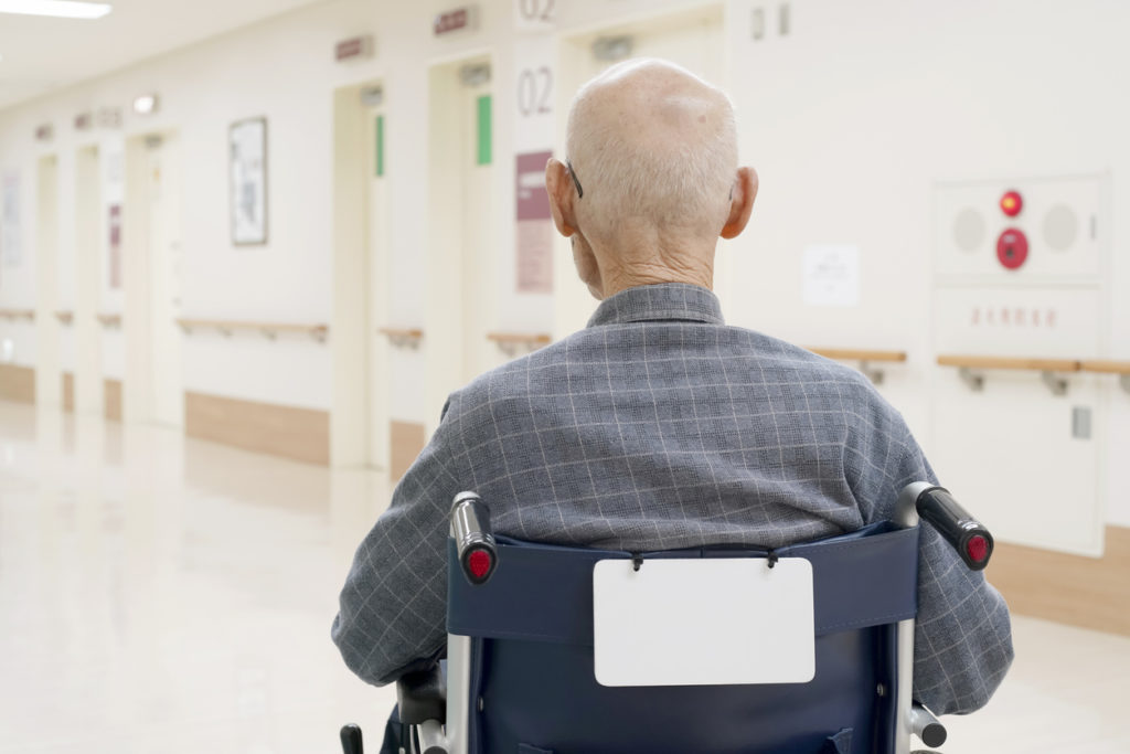 Back view of old man sitting on wheelchair