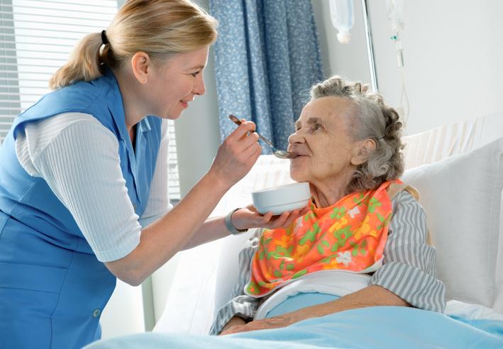 Helpful hospital nurse helping an elderly woman eat lunch
