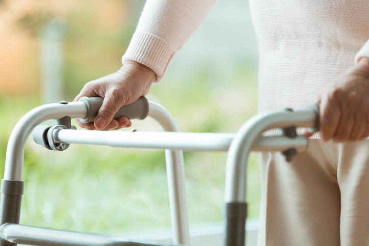 Senior person using walking frame