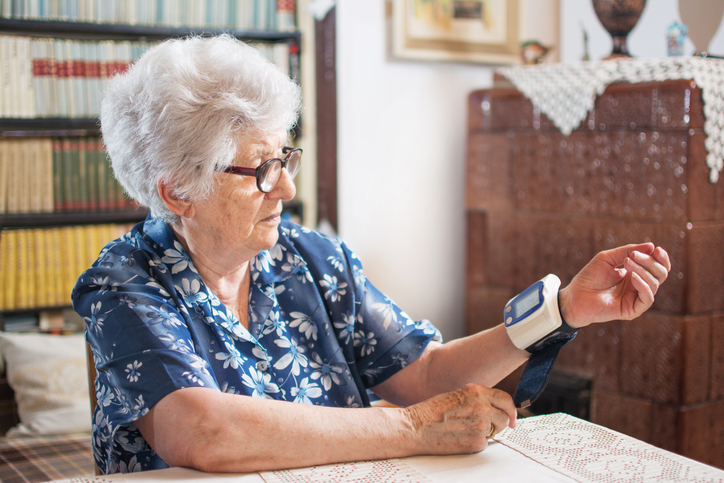 Senior woman measuring her blood pressure at home.