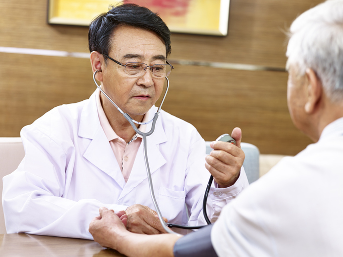 asian doctor checking blood pressure of a senior patient