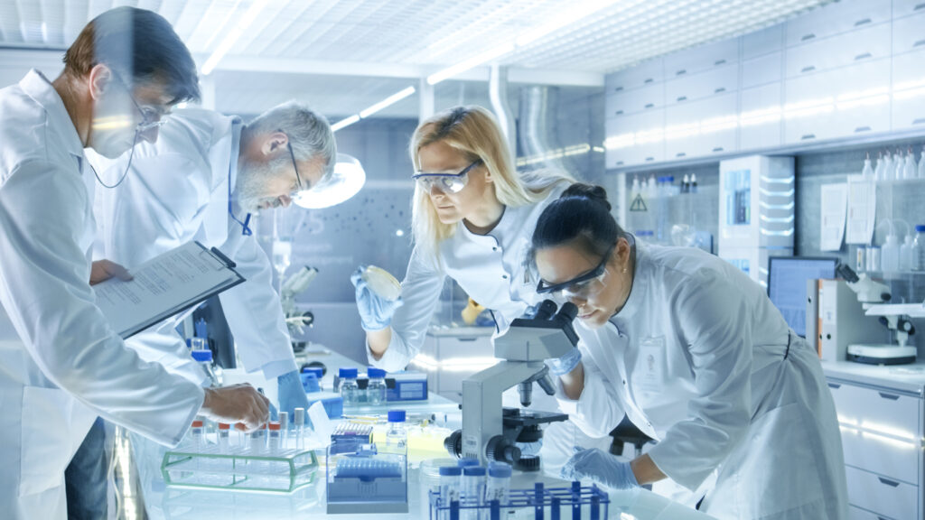 Team of Medical Research Scientists Work on a New Generation Disease Cure. They use Microscope, Test Tubes, Micropipette and Writing Down Analysis Results. Laboratory Looks Busy, Bright and Modern.