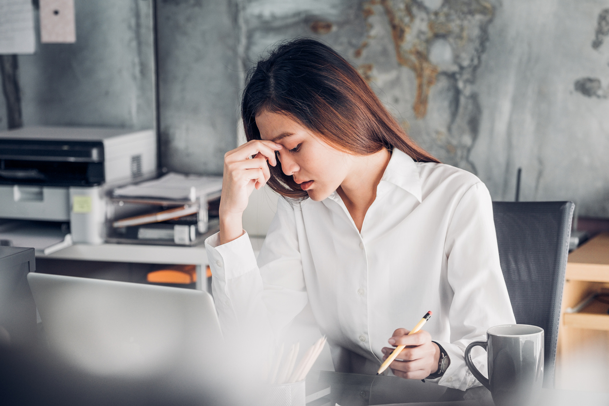 Frustrated Asian businesswoman cover her face with two hand and feel upset from work in front of laptop computer on desk at office,Stress office lifestyle concept.